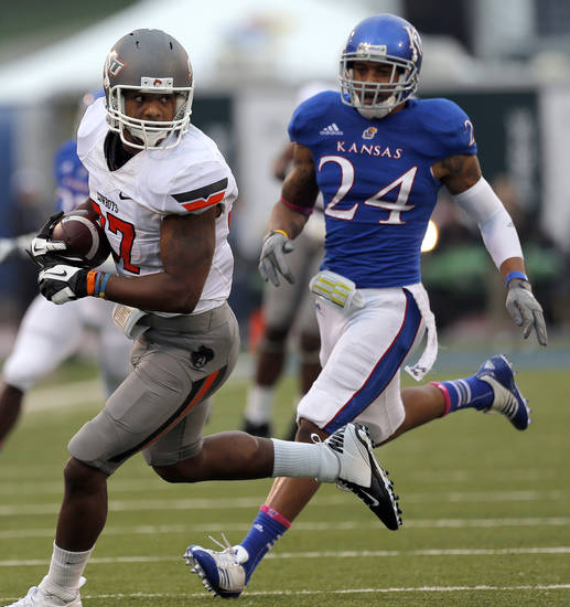 Oklahoma State's Tracy Moore (87) runs after making a catch as Kansas' Bradley McDougald (24) chases him down during the college football game between Oklahoma State University (OSU) and the University of Kansas (KU) at Memorial Stadium in Lawrence, Kan., Saturday, Oct. 13, 2012. Photo by Sarah Phipps, The Oklahoman
