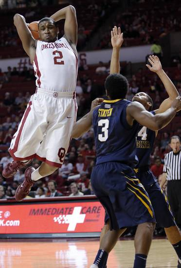 Oklahoma's Steven Pledger (2) pulls in a rebound over West Virginia 's Juwan Staten (3) and Jabarie Hinds (4) during the second half of the college basketball game between the University of Oklahoma Sooners (OU) and the West Virginia University Mountaineers (WVU) at the Lloyd Noble Center on Wednesday, March 6, 2013, in Norman, Okla. Photo by Chris Landsberger, The Oklahoman