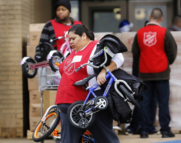 Maria Gonzalez carries a pair of bicycles from Crossroads Mall to a client's car. The Salvation Army and Feed the Children teamed to distribute bicycles and toys for children,  and handed out boxes of food for families at their annual distribution event Wednesday, Dec. 19, 2012. Salvation Army officials said 100 volunteers helped make the event go smoothly. The volunteers loaded bags of toys and bikes into vehicles of clients who had been pre-approved for assistance.  Many of the gifts were provided through the Salvation Army's Angel Tree program   Photo by Jim Beckel, The Oklahoman