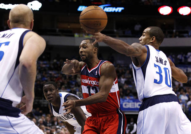 Washington Wizards' A.J. Price (12) makes a no-look pass between Dallas Mavericks' Chris Kaman, left back to camera, and Dahntay Jones (30) as Darren Collison, center rear, watches in the first half of an NBA basketball game, Wednesday, Nov. 14, 2012, in Dallas. (AP Photo/Tony Gutierrez)