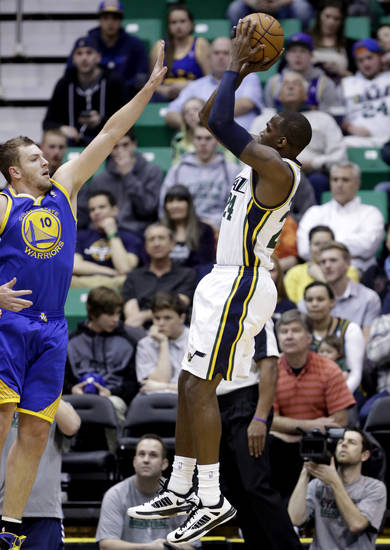 Utah Jazz's Paul Millsap, right, shoots against Golden State Warriors' David Lee (10) in the first quarter during an NBA basketball game Tuesday, Feb. 19, 2013, in Salt Lake City. (AP Photo/Rick Bowmer)