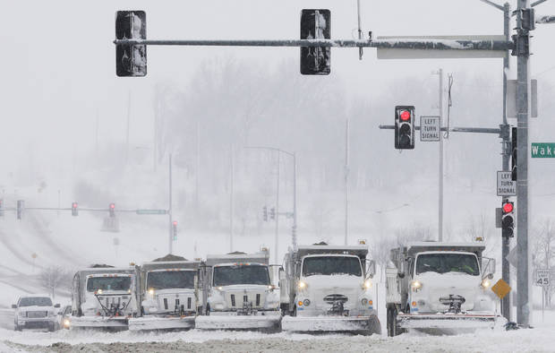 Snow plows stop for a traffic signal as they clear several lanes of West 6th Street in Lawrence, Kan., Sunday, March 24, 2013. Few signs of spring are being found in parts of the Midwest as a snowstorm brings heavy snow and high winds. (AP Photo/Orlin Wagner)