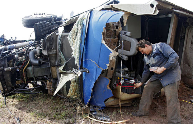 Armando Castillo finds personal items out of his truck that he was driving when it was swept off I-40 and destroyed by a tornado west of El Reno, Tuesday, May 24, 2011. Photo by Chris Landsberger, The Oklahoman