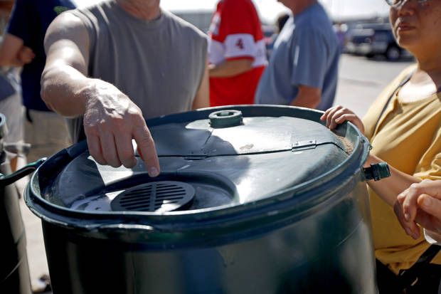 People look over an example of rain barrels as they wait in line to sign up for the next shipment of free rain barrels on Saturday, May 21, 2011. Over 80 barrels were given away before 9:30 as part of campaign to encourage wise water use. Photo by Bryan Terry, The Oklahoman