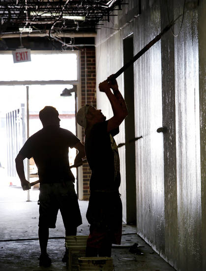 Workers apply a coat of paint to hallway walls at Central Junior High School in Moore. The district is remodeling the building to accommodate elementary students  displaced by the May 20 tornado.    Photo  by Jim Beckel, The Oklahoman. <strong>Jim Beckel - THE OKLAHOMAN</strong>
