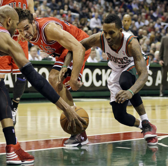 Milwaukee Bucks' Brandon Jennings, right, and Chicago Bulls' Joakim Noah (13) reach for a loose ball during the second half of an NBA basketball game Wednesday, Jan. 30, 2013, in Milwaukee. (AP Photo/Jeffrey Phelps)