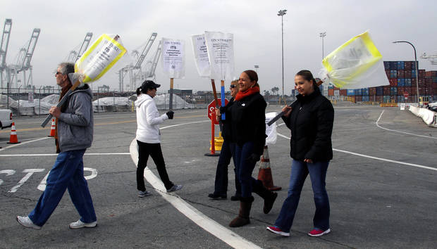 Clerical workers carry signs in protest at the Port of Long Beach, Calif. on Tuesday, December 4, 2012. Los Angeles Mayor Antonio Villaraigosa says both sides in a strike at the twin ports of Los Angeles and Long Beach have agreed to federal mediation. However, the union representing clerical workers says the strike now in its eighth day will continue. Clerical workers are striking 10 terminals at the nation&#039;s busiest port complex and dockworkers won&#039;t cross picket lines. (AP Photo/Nick Ut)