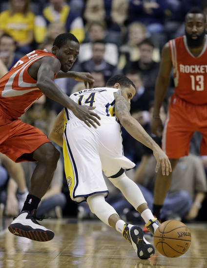 Houston Rockets' Patrick Beverley, left, stripes the basketball from Indiana Pacers' D.J. Augustin during the first half of an NBA basketball game Friday, Jan. 18, 2013, in Indianapolis. (AP Photo/Darron Cummings)