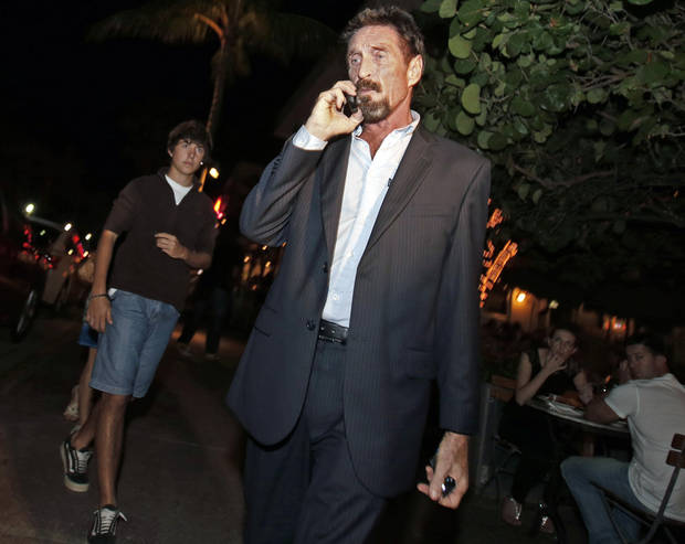 Anti-virus software founder John McAfee talks on his mobile phone as he walks on Ocean Drive in the South Beach area of Miami Beach, Fla., on his way to dinner Wednesday, Dec 12, 2012. McAfee arrived in the U.S. on Wednesday night after being deported from Guatemala, where he had sought refuge to evade police questioning in the killing of a man in neighboring Belize.(AP Photo/Alan Diaz)