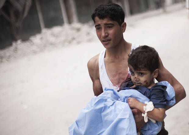 RETRANSMISSION FOR ALTERNATIVE CROP - A Syrian youth holds a child wounded by Syrian Army shelling near Dar El Shifa hospital in Aleppo, Syria, Thursday, Oct. 11, 2012. (AP Photo/ Manu Brabo)