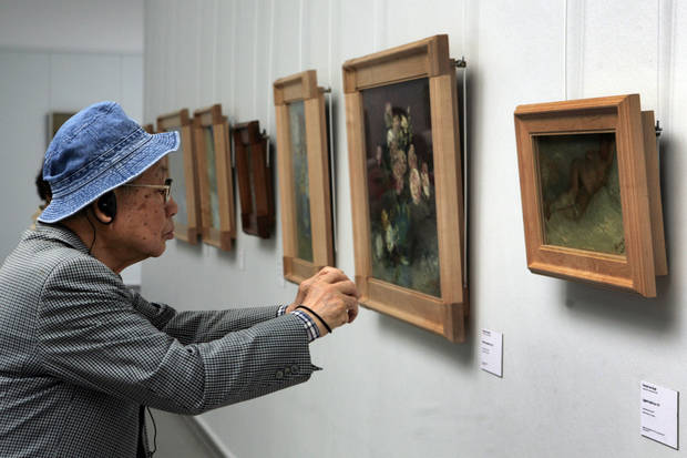 "A visitor inspects Vincent van Gogh's ""Nude Woman Reclining"" at the Kroeller-Museum in the Netherlands.   Photo by Peter Dejong, AP <strong>Peter Dejong - AP</strong>"