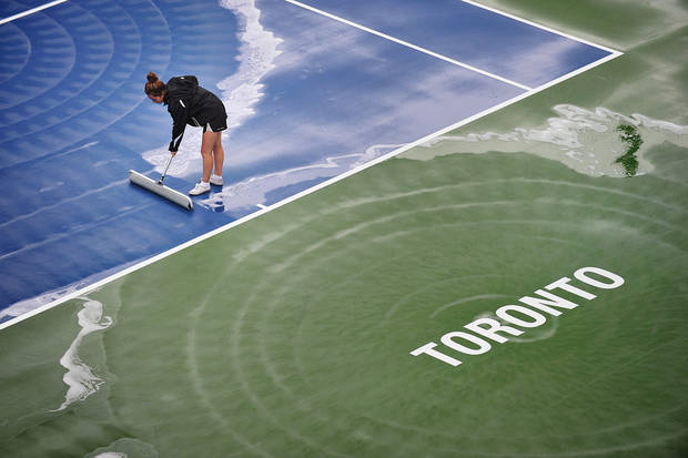 A worker dries the court during a rain delay at the Rogers Cup men's tennis tournament in Toronto on Thursday, Aug. 9, 2012. (AP Photo/The Canadian Press, Aaron Vincent Elkaim)