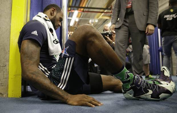 LeBron James sits on the floor, studying the post-game box score after the 2014 All-Star Game. (AP Photo)
