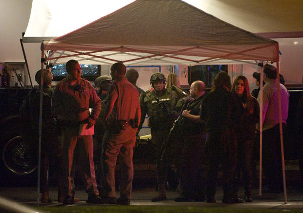 People confer at a command post representing several local police agencies south of the Cal State Fullerton campus, Wednesday, Dec. 12, 2012, in Fullerton, Calif. Students were placed on lock down as police searched for two suspects in a jewelry store robbery, who were considered armed and dangerous. (AP Photo/The Orange County Register, Bruce Chambers)