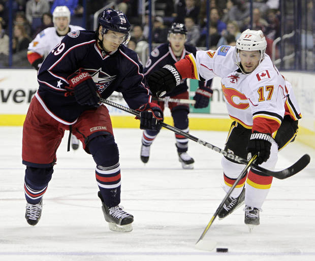 Calgary Flames' Blake Comeau (17) and Columbus Blue Jackets' Nick Holden (29) chase a loose puck during the first period of an NHL hockey game, Thursday, Feb. 7, 2013, in Columbus, Ohio. (AP Photo/Jay LaPrete)