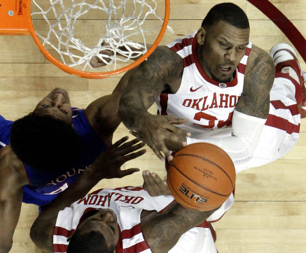 Oklahoma's Romero Osby, top, and Amath M'Baye (22) fight Kansas' Kevin Young (40) for a rebound of during the First half as the University of Oklahoma Sooners (OU) defeat the Kansas Jayhawks (KU) 72-66 in NCAA, men's college basketball at The Lloyd Noble Center on Saturday, Feb. 9, 2013 in Norman, Okla. Photo by Steve Sisney, The Oklahoman