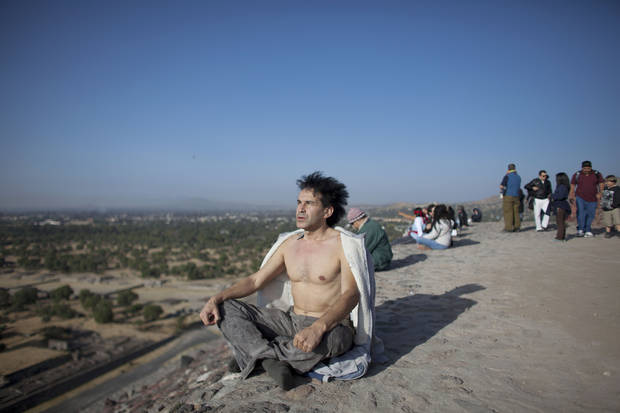 A man meditates from the top of the Pyramid of the Sun as the sun rises at the Teotihuacan archeological site in Teotihuacan, Mexico, Friday, Dec. 21, 2012. Many believe today is the conclusion of a vast, 5,125-year cycle in the Mayan calendar. Some have interpreted the prophetic moment as the end of the world, while others as believed it marked the birth of a new and better age. (AP Photo/Alexandre Meneghini)