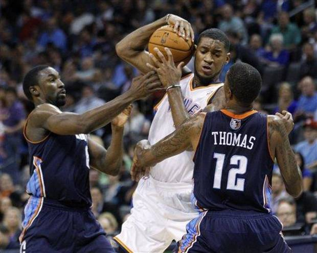 Oklahoma City Thunder forward Perry Jones, center, keeps the ball away from Charlotte Bobcats guard Ben Gordon (8) and forward Tyrus Thomas (12) during the second quarter of a preseason NBA basketball game in Oklahoma City, Tuesday, Oct. 16, 2012. Oklahoma City won 120-98. (AP Photo/Sue Ogrocki)