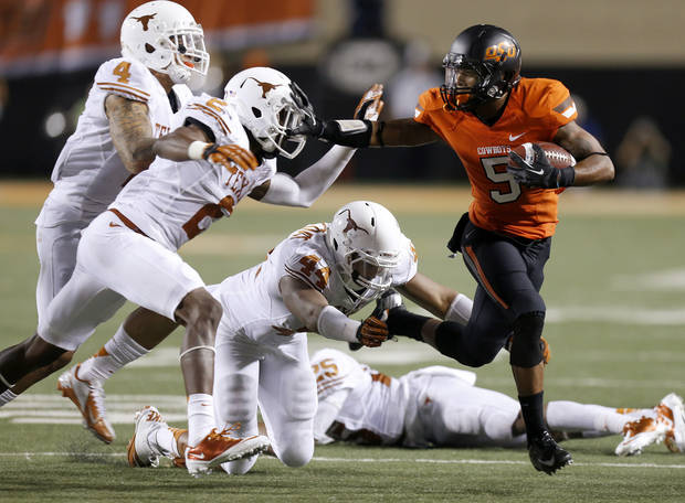 Oklahoma State's Josh Stewart (5) tries to get away from Texas' Kenny Vaccaro (4), Mykkele Thompson (2), and Jackson Jeffcoat (44)  during a college football game between Oklahoma State University (OSU) and the University of Texas (UT) at Boone Pickens Stadium in Stillwater, Okla., Saturday, Sept. 29, 2012. Oklahoma State lost 41-36. Oklahoma State lost 41-36. Photo by Bryan Terry, The Oklahoman
