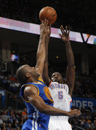Oklahoma City 's Kendrick Perkins (5) takes a shot over Golden State's Carl Landry (7) during an NBA basketball game between the Oklahoma City Thunder and the Golden State Warriors at Chesapeake Energy Arena in Oklahoma City, Sunday, Nov. 18, 2012.  Photo by Garett Fisbeck, The Oklahoman