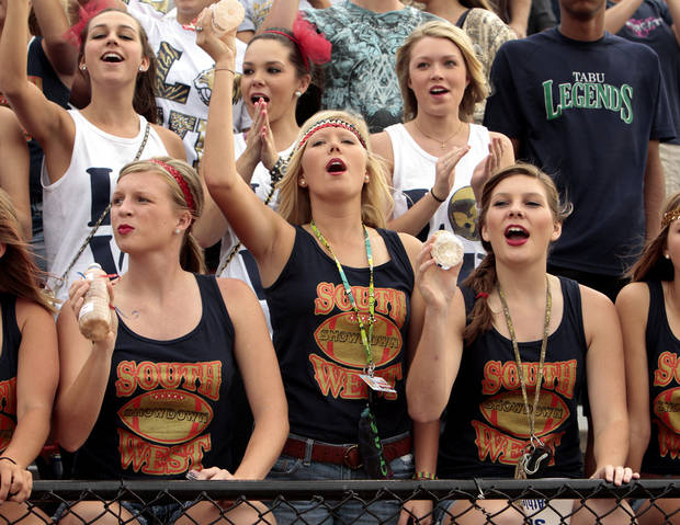 Southmoore fans Courtney Bone, Cassidy Herbster and Kyra Gilbert cheer as the Sabercats play the Westmoore Jaguars in high school football on Friday, Sept. 7, 2012, in Moore, Okla.  Photo by Steve Sisney, The Oklahoman