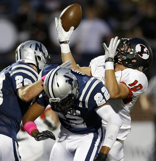 Yukon's Brandon Andraszek can't make the catch beside Edmond North's Jake Hobbs, left, and Dante Sanders during their high school football game at Wantland Stadium in Edmond, Okla., Thursday, October 4, 2012. Photo by Bryan Terry, The Oklahoman