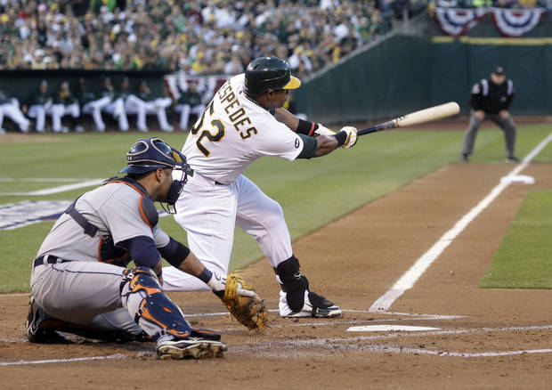 Oakland Athletics' Yoenis Cespedes swings on a single that scored Coco Crisp in the first inning of Game 3 of the Athletics' American League division baseball series against the Detroit Tigers in Oakland, Calif., Tuesday, Oct. 9, 2012. (AP Photo/Marcio Jose Sanchez)