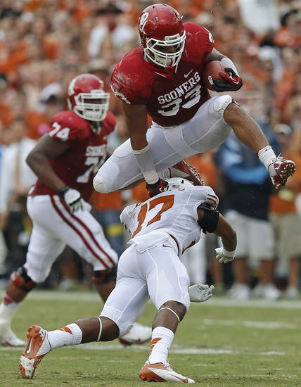 OU's Trey Millard (33) leaps over UT's Adrian Phillips (17) during the Red River Rivalry college football game between the University of Oklahoma (OU) and the University of Texas (UT) at the Cotton Bowl in Dallas, Saturday, Oct. 13, 2012. Photo by Bryan Terry, The Oklahoman