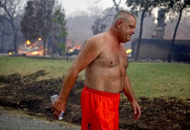 FIRE: George Reich walks past the burning remains of his neighbor's house on Blackjack Lane in Edmond, Okla., Saturday, August 6, 2011. Reich's home was also a complete loss. Photo by Bryan Terry, The Oklahoman ORG XMIT: KOD