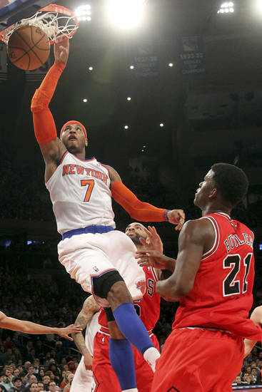 Chicago Bulls' Jimmy Butler (21) watches as New York Knicks' Carmelo Anthony scores a basket during the first half of an NBA basketball game on Friday, Dec. 21, 2012, at Madison Square Garden in New York. (AP Photo/Mary Altaffer)