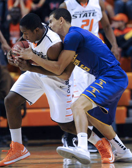 Oklahoma State guard Jean-Paul Olukemi, left, steals the ball from Tennessee Tech guard Jeremiah Samarrippas, right, during the first half of an NCAA college basketball game in Stillwater, Okla., Saturday, Dec. 22, 2012.  (AP Photo/Brody Schmidt)