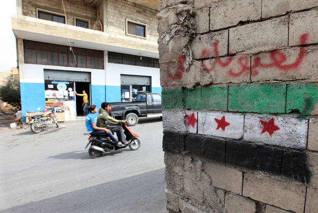 In this Tuesday, Oct. 2, 2012 photo, a Syrian revolution flag painted on a wall in Arsal, a Sunni Muslim town eastern Lebanon near the Syrian border, has become a safe haven for war-weary Syrian rebels and hundreds of refugee families. Many in Arsal support the rebels, but the town�s stand is risking heightened tensions with its Shiite Muslim neighbors in an area controlled by Hezbollah, a militia that backs the Syrian regime. Deepening sectarian rifts are one of the ways in which Syria�s 18-month-old conflict is destabilizing an already volatile region. (AP Photo/Bilal Hussein)