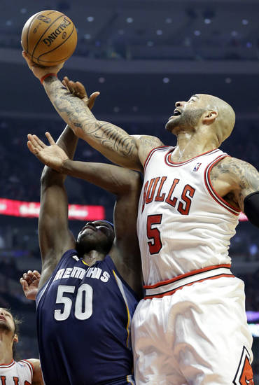 Chicago Bulls forward Carlos Boozer, right, battles for a rebound with Memphis Grizzlies forward Zach Randolph during the first half of an NBA basketball game in Chicago on Saturday, Jan. 19, 2013. (AP Photo/Nam Y. Huh)