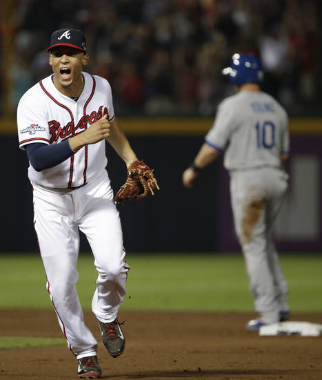 Atlanta Braves shortstop Andrelton Simmons, left, reacts after he turned a double play against the Los Angeles Dodgers in the seventh inning during Game 2 of the National League division series on Friday, Oct. 4, 2013, in Atlanta. (AP Photo/John Bazemore)