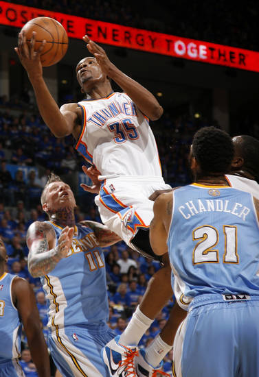 Oklahoma City's Kevin Durant (35) goes to the basket between Denver's Chris Andersen (11) and Wilson Chandler (21) during the NBA basketball game between the Denver Nuggets and the Oklahoma City Thunder in the first round of the NBA playoffs at the Oklahoma City Arena, Sunday, April 17, 2011. Photo by Bryan Terry, The Oklahoman