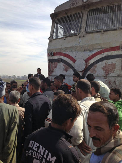 Egyptians gathered at the scene of a train crash that killed at least 47 people, most of them children, near Assiut in southern Egypt, Saturday, Nov. 17, 2012. The bus was carrying more than 50 children between 4 and 6 years old when it was hit near al-Mandara village in Manfaloot district in the province of Assiut, a security official said, adding that it appears that the railroad crossing was not closed as the train sped toward it. (AP Photo/Mamdouh Thabet)