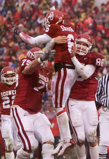 Mike Skinner, left, and Trent Smith, right, lift Antwone Savage after a touchdown against Colorado in 2002. PHOTO BY DOUG HOKE, THE OKLAHOMAN ARCHIVE