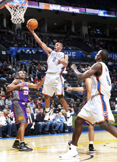 Oklahoma City's Russell Westbrook, center, drives to the basket past Phoenix's Grant Hill, left, during preseason action at the Ford Center on Monday. Westbrook was one assist away from a triple-double.  Photo by Chris Landsberger, The Oklahoman