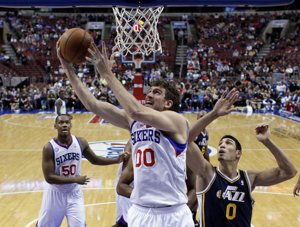 Philadelphia 76ers' Spencer Hawes (00) goes up for a shot as Utah Jazz's Enes Kanter (0), of Turkey, defends in the first half of an NBA basketball game on Friday, Nov. 16, 2012, in Philadelphia. (AP Photo/Matt Slocum)