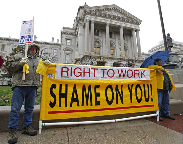 "FILE - In this Nov. 22, 2011 file photo, Joe Lubbers, left, and Rick McKee display a sign in front of the Statehouse before start of Organization Day in Indianapolis. Union members rallied at the Statehouse ahead of a 2012 session that was to be dominated by ""right-to-work"" legislation. A unionized job once meant a secure path to a middle class life. Labor unions are still big political players. But they have seen a steady decline in membership and clout since their heyday in the 1950s. (AP Photo/Darron Cummings)"