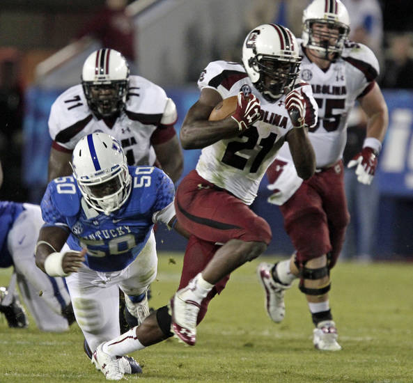 South Carolina tailback Marcus Lattimore (21) runs away from Kentucky's Mike Douglas (50) during the second half of an NCAA college football game in Lexington, Ky., Saturday, Sept. 29, 2012. No. 6 South Carolina came from behind to beat Kentucky 38-17. (AP Photo/Garry Jones)