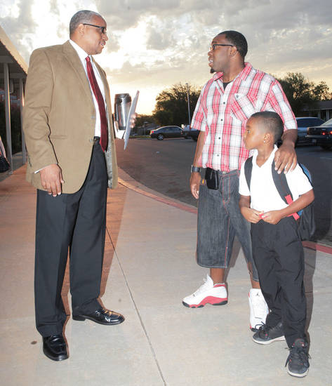 Organizer Calvin Williams visits Friday with Markis Frederick and his son, Tishaun, 6, during �Take Your Child to School Day� at Martin Luther King Elementary School. Photos By David McDaniel, The Oklahoman