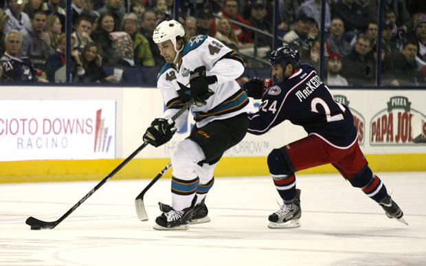 San Jose Sharks' Matt Pelech (42) races past Columbus Blue Jackets' Derek MacKenzie during the first period of an NHL hockey game, Monday, Feb. 11, 2013, in Columbus, Ohio. (AP Photo/Mike Munden)