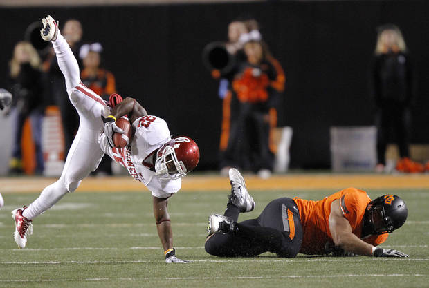 Oklahoma's Roy Finch (22) is upended by Oklahoma State's Jamie Blatnick (50) during the Bedlam college football game between the Oklahoma State University Cowboys (OSU) and the University of Oklahoma Sooners (OU) at Boone Pickens Stadium in Stillwater, Okla., Saturday, Dec. 3, 2011. Photo by Chris Landsberger, The Oklahoman
