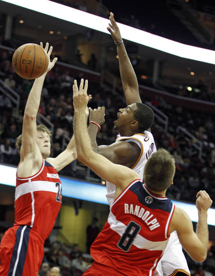 Cleveland Cavaliers' Tristan Thompson (13) loses control of the ball under pressure from Washington Wizards' Jan Vesely (24) and Shavlik Randolph (8) during the second quarter of an NBA preseason basketball game Saturday, Oct. 13, 2012, in Cleveland. (AP Photo/Tony Dejak)