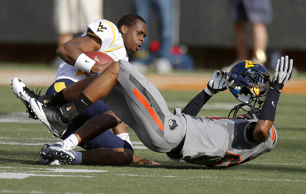 Oklahoma State's Lyndell Johnson (27) brings down West Virginia's Geno Smith (12) during a college football game between Oklahoma State University (OSU) and West Virginia University at Boone Pickens Stadium in Stillwater, Okla., Saturday, Nov. 10, 2012. Photo by Bryan Terry, The Oklahoman