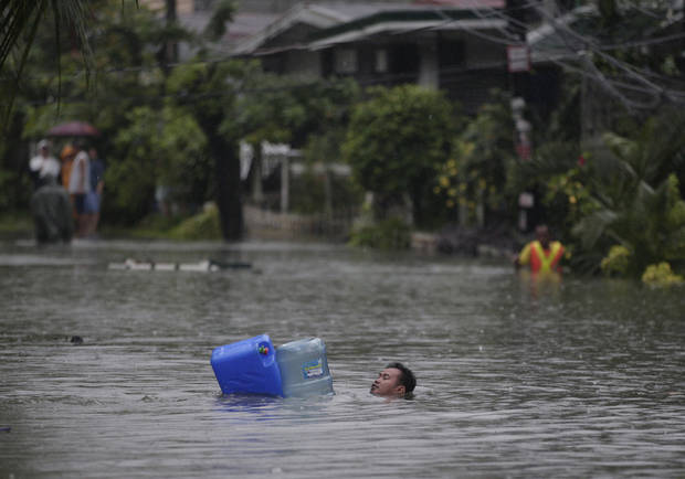 A man crosses deep floodwaters using water containers as floaters in suburban Quezon City, north of Manila, Philippines on Tuesday Aug. 7, 2012. Torrential rains pounding the Philippine capital on Tuesday paralyzed traffic as waist-deep floods triggered evacuations of tens of thousands of residents and the government suspended work in offices and schools.(AP Photo/Aaron Favila)