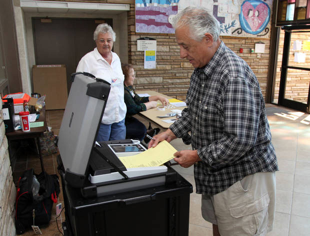 Don Lomangino inserts his ballot at the John Knox Church precinct for the runoff election as precinct worker Talca Harris watches in Tulsa, Okla., Tuesday, Aug. 28, 2012. (AP Photo/Tulsa World, Stephen Pingry) ORG XMIT: OKTUL101