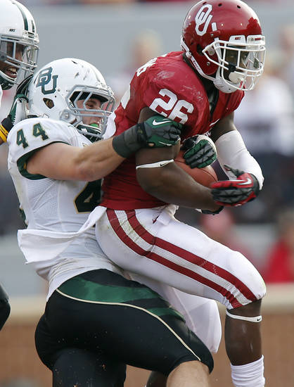 Oklahoma's Damien Williams (26) drags Baylor's Bryce Hager (44) on a run during the college football game between the University of Oklahoma Sooners (OU) and Baylor University Bears (BU) at Gaylord Family - Oklahoma Memorial Stadium on Saturday, Nov. 10, 2012, in Norman, Okla.  Photo by Chris Landsberger, The Oklahoman