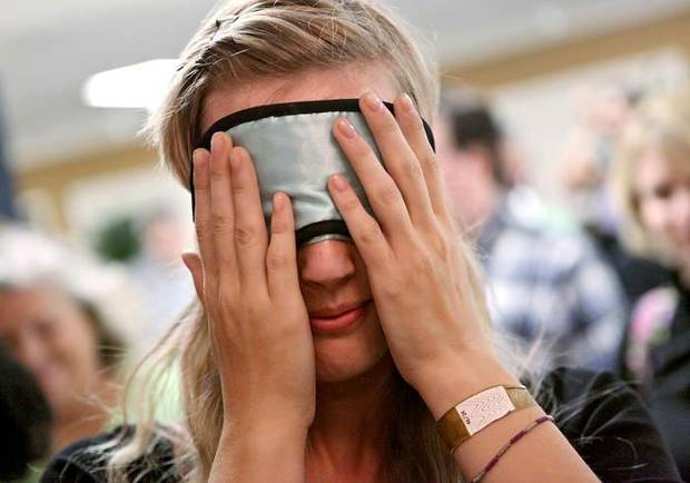 Rebecca Tyberg, a junior at Piedmont High School, puts on her blindfold as she enters a ballroom for Dining in the dark at the University of Central Oklahoma in Edmond on Monday, Sept. 28, 2009. By John Clanton, The Oklahoman ORG XMIT: KOD
